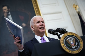 US President Joe Biden holds a copy of his administration's National COVID-19 Strategy booklet as he speaks about his efforts to address the pandemic in the US.