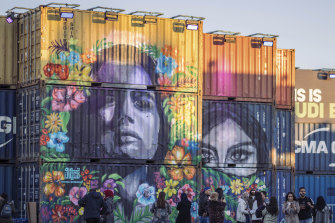 People walk behind a concert stage created from shipping containers and painted by local graffiti artists, during the MDL Beast Festival, a three-day musical extravaganza designed to change perceptions of the Kingdom.