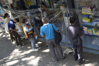 Customers order medicines through a protective plastic sheet at a pharmacy in Bangkok on Thursday.