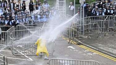 Police officers use a water cannon on a lone protester near the government headquarters in Hong Kong on Wednesday.
