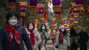 Chinese women and a child all wear protective masks as they walk under decorations in a park after celebrations for the Chinese New Year and Spring Festival were cancelled by authorities on January 25, 2020 in Beijing, China.