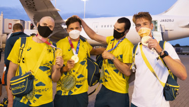Gold medallist rowers, from left, Spencer Turrin, Alexander Hill, Alexander Purnell and Jack Hargreaves hold up their Tokyo Olympic medals on arrival back in Sydney on Sunday.
