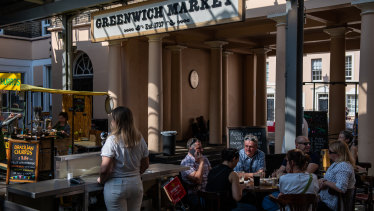 A group of six people drink alcohol at a pub in Greenwich market in London, England.