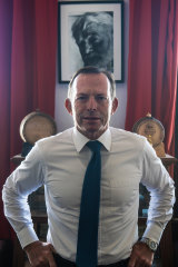 Former prime minister, Tony Abbott, in front of a portrait of Ernest Hemingway.