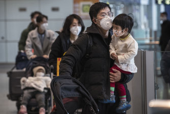 Passengers wear protective masks as they walk in the arrivals area at Beijing Capital Airport.