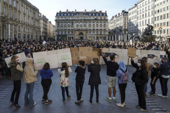 People hold a large banner that reads: 'Don't touch my teacher', in front of the crowd in Lyon, central France, on Sunday.