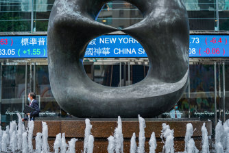 A sculpture stands in front of a stock ticker at the Exchange Square complex, which houses the Hong Kong Stock Exchange. The struggle to maintain confidence in Hong Kong's future is manifesting in its stock and currency markets.