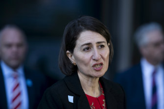 Premier Gladys Berejiklian, flanked by education officials, announces a gradual return to classrooms