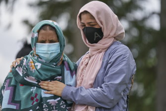 Khalida Ashram and her daughter Anila mourn at the scene of an attack on Monday, involving a driver accused of plowing a ute into an immigrant family of five in London, Ontario.