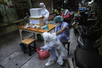 A health worker in Bangkok takes off the PPE gear, while her colleague seals the foam box containing swab samples.