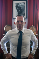 Former prime minister, Tony Abbott, in front of a portrait of Ernest Hemingway.