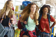 Three female backpacking friends make their way to depart for the next part of their journey. They are carrying their backpacks, checking the timetable and having a laugh. iStock image for Traveller. Re-use permitted. Young female backpackers at airport.
