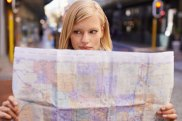 Shot of a young woman holding a map while touring abroad iStock image for Traveller. Re-use permitted. Tourist reading map.