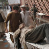 A wounded man is brought by stretcher into a hospital after a bombing at a mosque during Friday prayers.