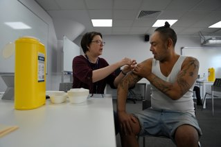 Jayden Poi, right, receives his COVID-19 vaccine from nurse Caryn Gottcent at Woolloomooloo on Thursday.
