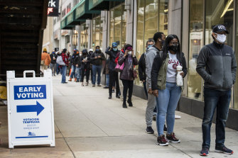 Hundreds of people wait in line to vote early in Chicago on Thursday.