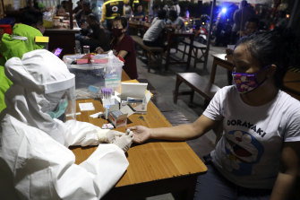 Medical workers take blood samples from a customer during a rapid test for the new coronavirus at a cafe in Surabaya, East Java, Indonesia.