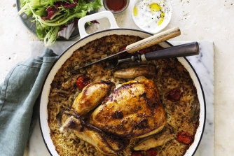 Roast chicken on baked rice with tomato, cumin and bay leaves.
