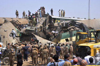 Rescuers search for survivors amid the wreckage of the trains in Ghotki.