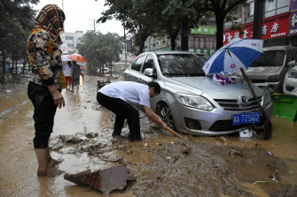 Residents clean up the aftermath of a flood in Mihe Town of Gongyi City, in central China's Henan province.