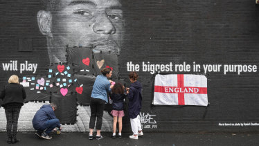 Residents put messages of support over racially-charged graffiti on a Marcus Rashford mural in Manchester.