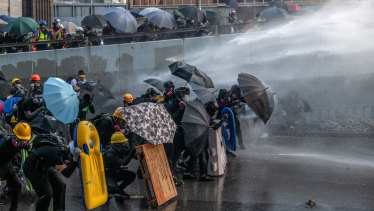 Pro-democracy protesters are hit by a water cannon during clashes at the Central Government Offices in Hong Kong, China.