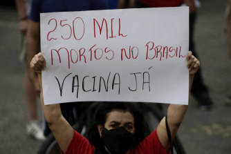"A demonstrator holds a sign written in Portuguese that reads ""250 thousand dead in Brazil, Vaccine Now."""