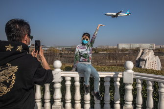 A woman wearing a protective face mask poses for photos as a plane lands at the Capital International Airport in Beijing. Chinese students and expatriates were discouraged from returning home during the pandemic.