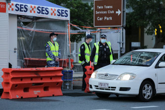 Police and defence personnel check on cars crossing the border at Coolangatta.