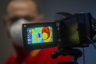 An airline passenger is checked with a thermal imaging camera for signs of coronavirus.