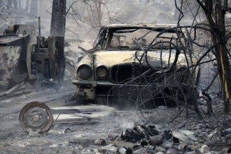 The burnt out shell of a Jaguar vehicle sits in the ruins of a smouldering house on Old Bar road near Taree on Saturday.