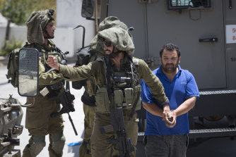 Israeli soldiers make one of several arrests of Palestinians on May 12 after a soldier of their occupation force was killed by a rock thrown from a rooftop in the West Bank village of Yabad.