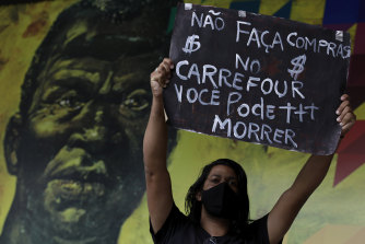 """A protester holds up the Portuguese message """"Don't shop at Carrefour, you could die"""", in front of an image of Brazilian runaway slave hero Zumbi dos Palmares during a protest over the killing of black man João Alberto Silveira Freitas at a Carrefour supermarket."""