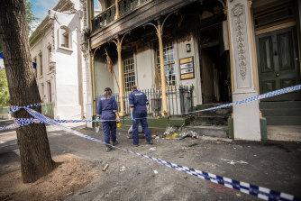 Police inspect the fire damage on Sunday.