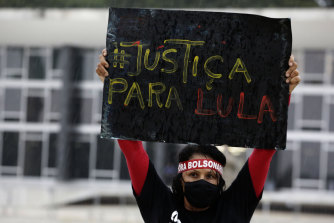 """A demonstrator with a headband that reads """"Bolsonaro out"""" raises a sign that reads """"Justice for  Lula"""" in Brasilia on Monday."""