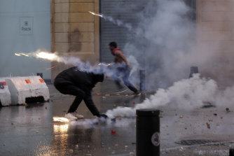 Protesters attempt to throw tear-gas canisters back at riot police.