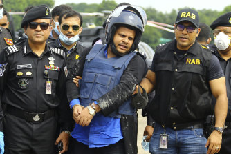 Mohammed Shahed, centre, the owner of two hospitals that issued thousands of fake coronavirus test reports, after being arrested in Dhaka, Bangladesh.