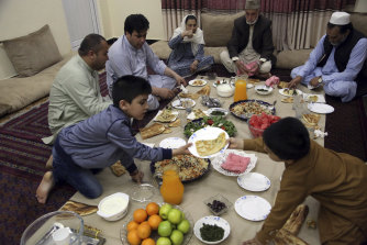 An Afghan family breaks their fast with the Iftar meal at sundown, on the first day of the holy month of Ramadan, in Kabul, Afghanistan.