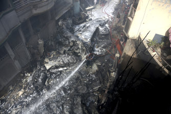 Fire brigade staff try to put out fire caused by plane crash in Karachi, Pakistan, on Friday.