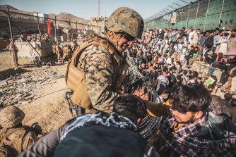 A US Marine assists during an evacuation at Hamid Karzai International Airport in Kabul.