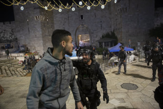 An Israeli policeman shouts at a Palestinian to move after clashes at the al-Aqsa Mosque compound on Friday.