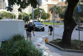 A cleaning crew at one of two CBD crime scenes set up after the fatal stabbing.