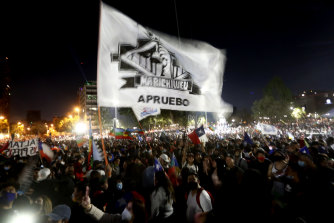"People hold a flag that reads ""Approval"" during a celebration as they wait for the official results of the referendum for a new constitution in Santiago on Sunday."