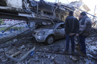 Residents survey the aftermath of airstrikes in Idlib on Saturday.