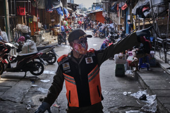 A public order policeman clears an area of clothing shops, stalls and customers at the Tanah Abang textile market in a cat and mouse game of closing and reopening the stalls on Friday.