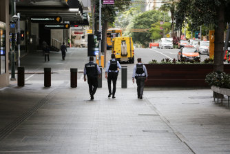 Police patrol empty streets during Brisbane's lockdown, the strictest of the pandemic so far.