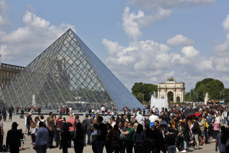Tourists wait in line to visit the Louvre museum as it reopens in May.