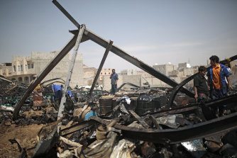 Workers salvage oil canisters from the wreckage of a warehouse hit by Saudi-led air strikes in Sanaa, Yemen on July 2.