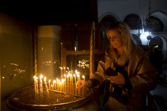 A visitor places candles at the Church of the Nativity in Bethlehem, built at the site where many Christians believe Jesus was born.
