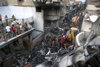 Volunteers and soldiers look for survivors of a plane crash in a residential area of Karachi, Pakistan.